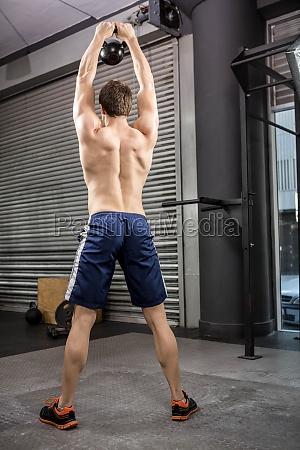 rear view of shirtless man lifting