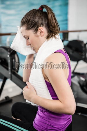 fit brunette wiping sweat with towel