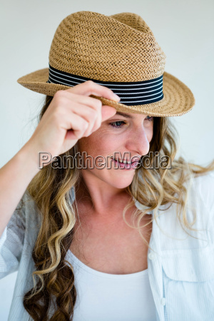 woman wearing a straw fedora peering