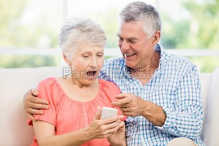 smiling senior couple using smartphone