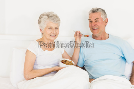 happy senior woman feeding her husband