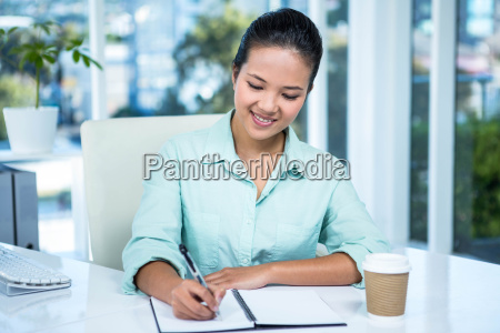 smiling businesswoman writing notes with a