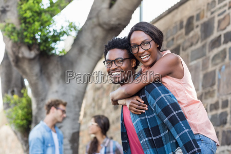young man giving piggyback to woman