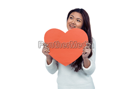 smiling asian woman holding paper heart
