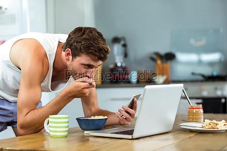 man having breakfast while using mobile