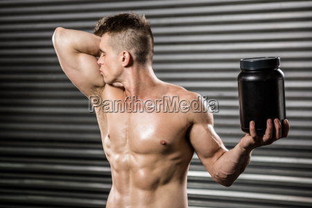 shirtless man kissing biceps and holding