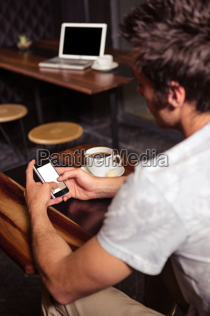 hipster man using smartphone while drinking