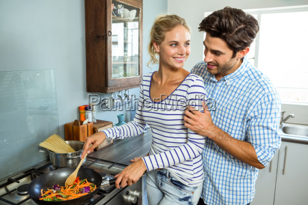young couple preparing food together in