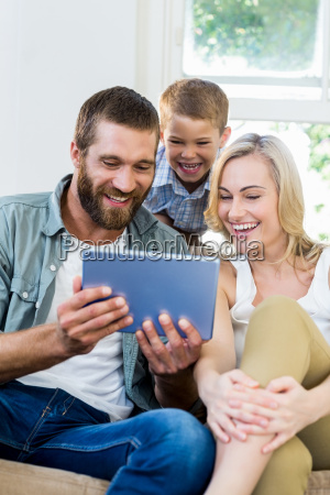 family using digital tablet in living