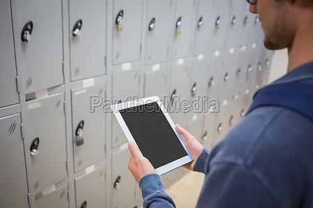 student using digital tablet in locker