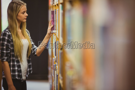 blonde student reading book next to