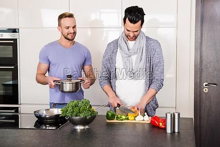 smiling gay couple preparing food