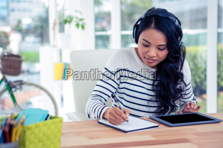 smiling asian woman with headphones writing