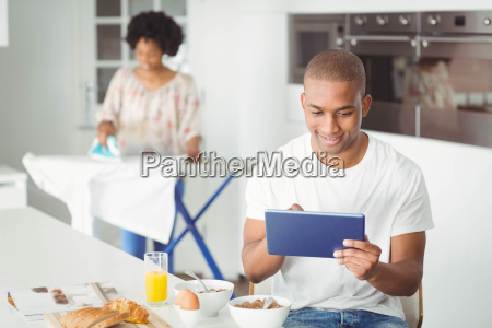 young man using tablet in kitchen