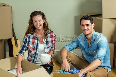 young couple unpacking carton boxes