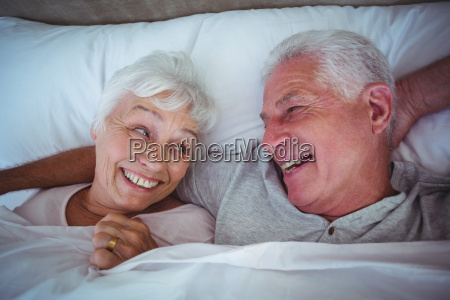 laughing senior couple lying on bed