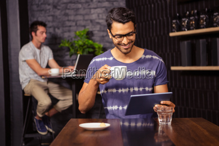 man using a tablet and drinking