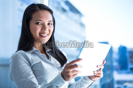 smiling businesswoman holding tablet and looking