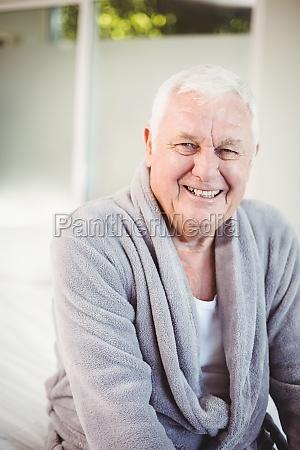 smiling senior man in bedroom at