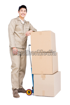 delivery man standing beside luggage trolley