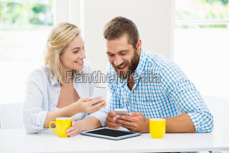 smiling couple using a mobile phone