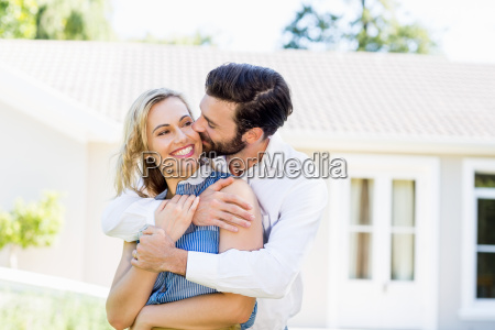 young man kissing on womans cheek