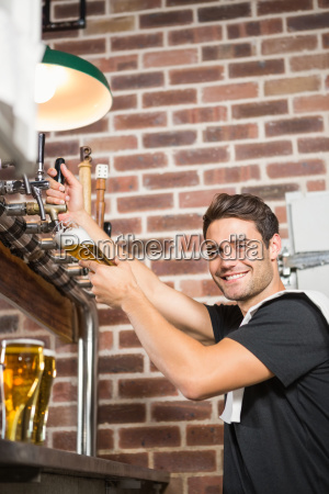 handsome barman pouring a pint of
