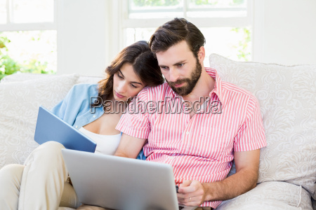 couple using digital tablet and laptop