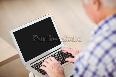 senior man using laptop in living