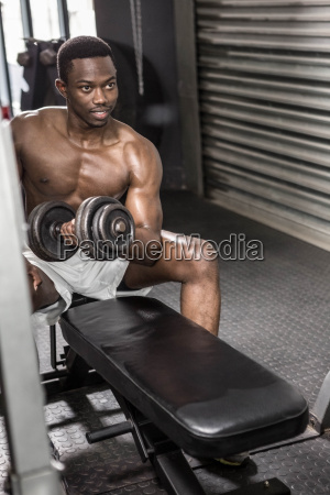 shirtless man lifting dumbbell on bench