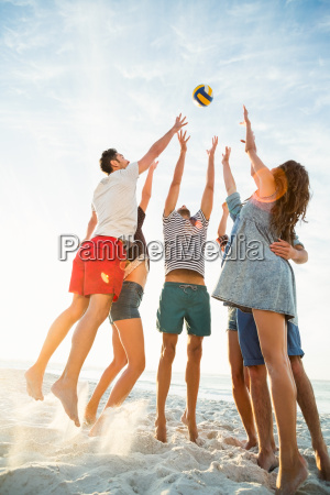friends trying to catch volley ball