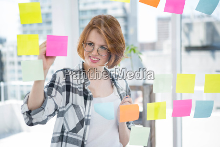 smiling hipster woman sticking notes on