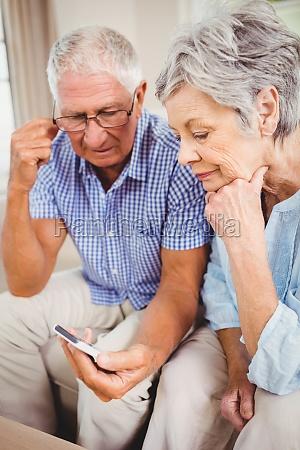 sad senior couple looking at mobile