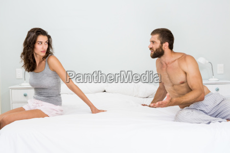 man arguing with woman on bed