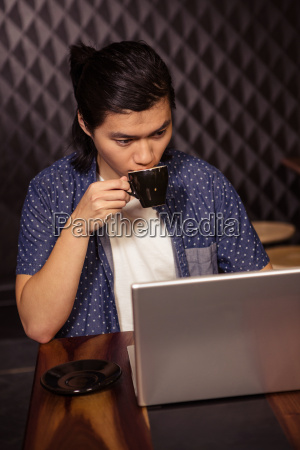 man using a laptop and drinking
