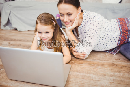 smiling daughter using laptop with mother