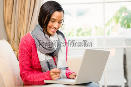smiling brunette using laptop and holding