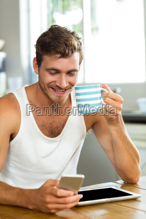 happy man having coffee while using