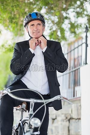 front view of businessman tying helmet