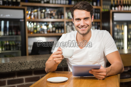 handsome man using tablet and having