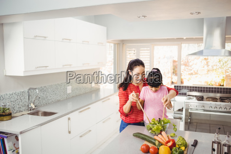 smiling mother and daughter preparing vegetable
