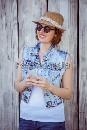 smiling hipster woman on her smartphone