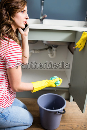 woman using mobile phone while cleaning