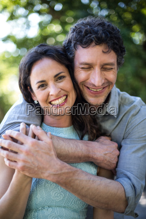 portrait of smiling wife being hugged