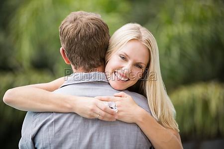 smiling young woman hugging man