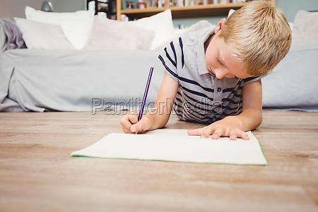 boy writing in book while lying