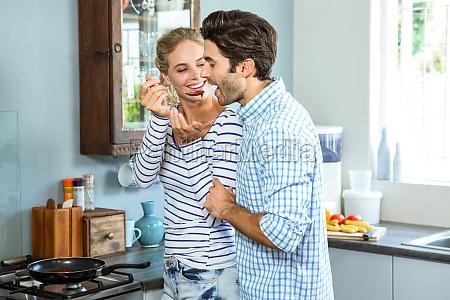 smiling woman letting man taste a
