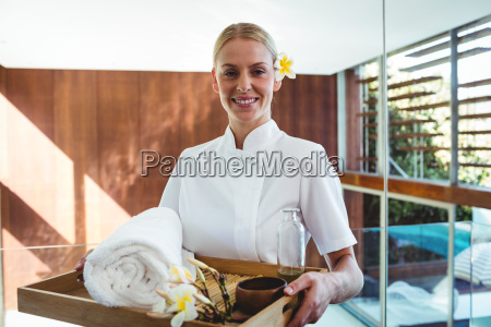 smiling masseuse holding a tray