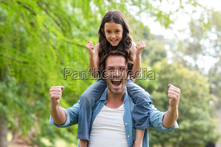 father carrying her daughter on shoulder