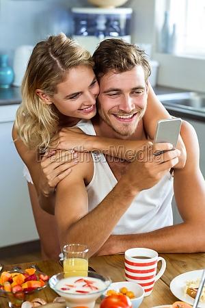 woman embracing man using mobile phone